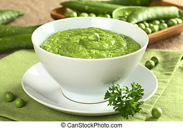 Fresh green pea soup with pea seeds and pea pods around...
