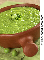 Fresh green pea soup in rustic bowl