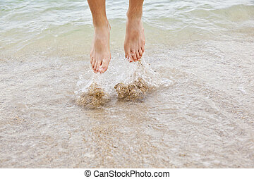 feet of boy jumping into the water at the beach