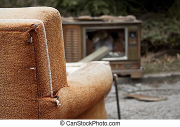 Trash on TV - Discarded furniture at a dump site.