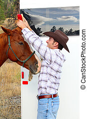 Grooming - Young cowboy grooming his horse at the trailor