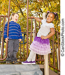 Children playing on playground - Young African-American girl...
