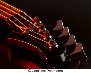 bass guitar detail - detail of a bass guitar with red light...