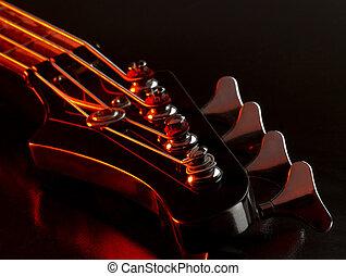 bass guitar detail - detail of a bass guitar with red light...