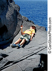 happy boy lies on the rock and is greating by raising the...