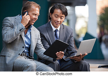 Businessmen using electronic gadgets - Businessmen using...