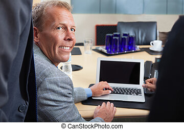 Mature man using laptop in office