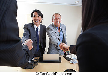 Business people shaking hands - Smiling business people...
