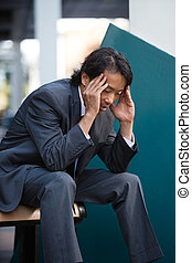 Businessman Stress - Business man sitting on bench outdoors...
