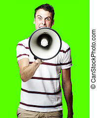 man shouting - portrait of young man shouting with megaphone...