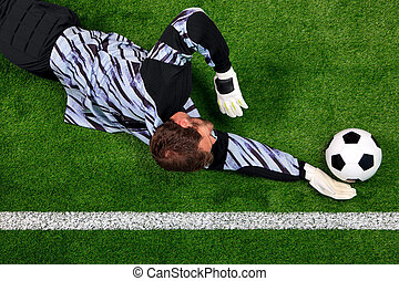 Overhead shot of a goalkeeper diving to save the ball -...