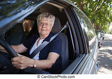 Old woman driving car - Portrait of smiling old woman...
