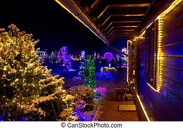 Christmas fantasy - trees and wooden house in lights on a...