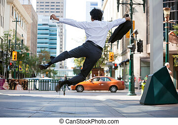 Business Man Jumping in Air - Rear view of business man...