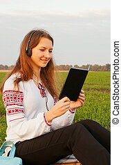 Young lady with e-book reader sitting on grass