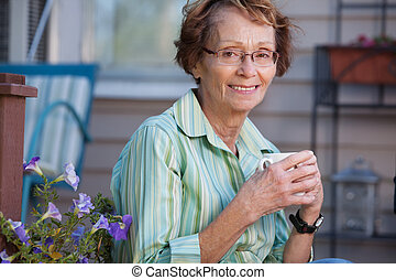 Senior Woman with Warm Drink Outdoors - Portrait of smiling...