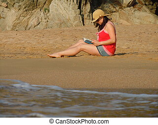 reading on the beach - young woman sitting on the beach...