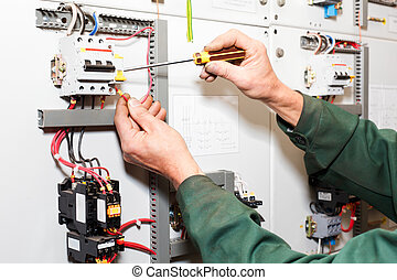Electrician`s hands working with screwdriver in cables and...