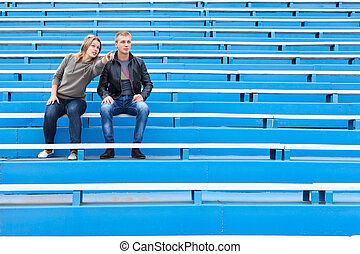 Man and woman sitting on grandstand - Man and woman sitting...