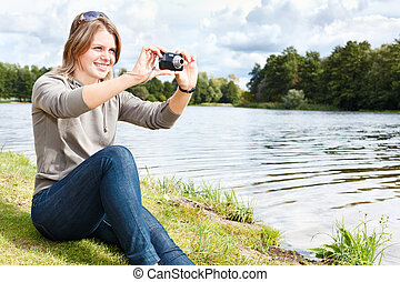 Young beautiful woman photographing