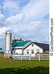farm house with field and silo in beautiful landscape