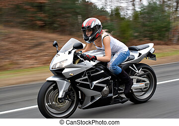 Speeding Motorcycle Woman - A woman drives a motorcycle at...