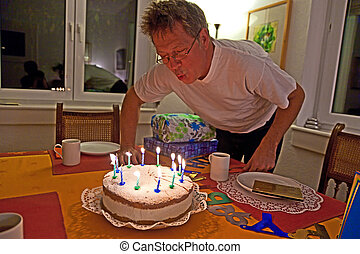 man blows out his birthday cake - a man blows out his...