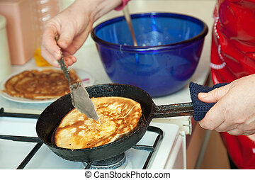 Cook hands cooking pancakes on griddle