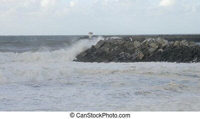 Big waves on a jetty with many concrete blocks