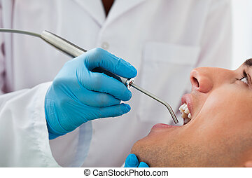 Suction Tool at Dentist - Dentist working on patient at...