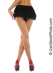 Beautiful female legs in red shoes and skirt