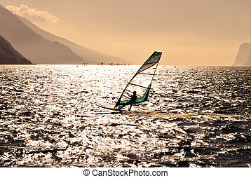 windsurfer panorama silhouette against a sparking lake of...
