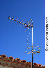 Television antenna on a tiled roof over blue sky