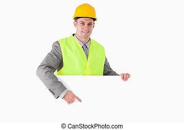 Smiling builder pointing at something
