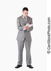 Portrait of a businessman taking notes against a white...