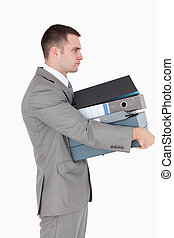Portrait of a businessman holding a stack of binders against...