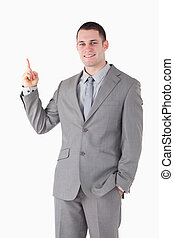 Portrait of a smiling young businessman pointing at something