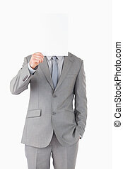 Portrait of a businessman hiding his face behind a blank...