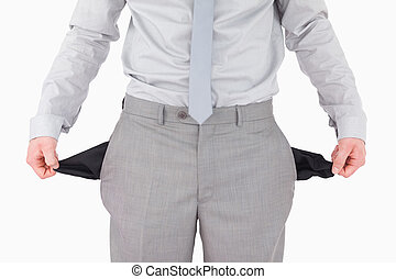 Businessman showing his empty pockets against a white...