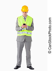 Portrait of a young builder using his cellphone against a...