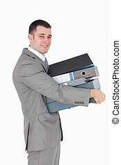 Portrait of a young businessman holding a stack of binders...