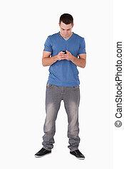 Portrait of a man sending text messages against a white...