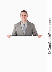 Portrait of a businessman behind a blank panel