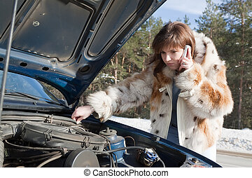 Young girl repairing the car - woman looking under the car...
