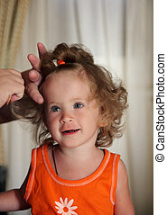 combing hair little girl - little girl combing hair by...