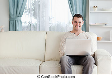 Man using a laptop while sitting on a sofa in his living...