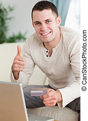 Portrait of a man purchasing online with the thumb up