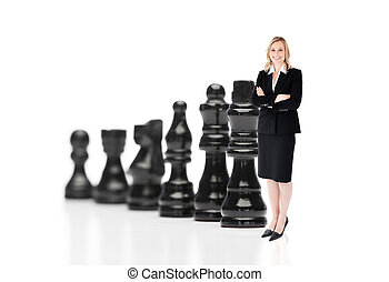 Businesswoman in front of black chess pieces on white...