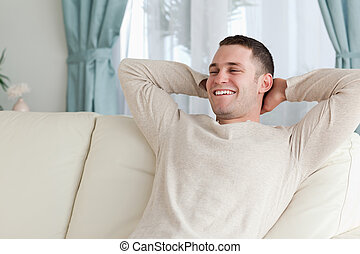 Laughing man relaxing on a couch