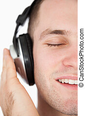 Close up of a serene man listening to music against a white...